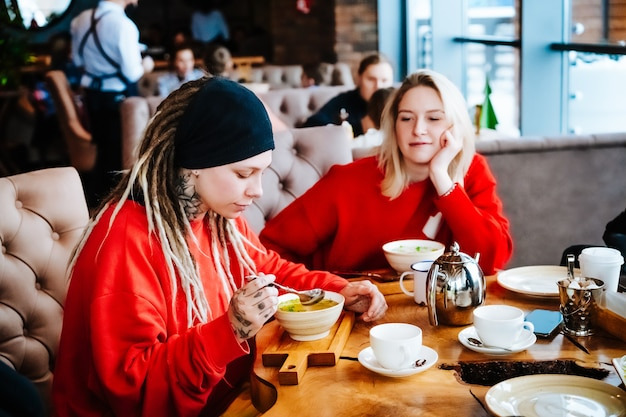 Красивая андрогинная девушка с дредами и татуировками и блондинка в красных свитерах едят суп за деревянным столом в кафе