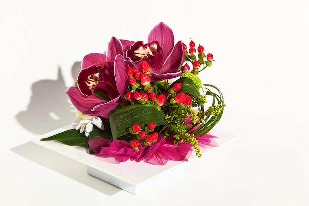 白い背景の上の新鮮な花のチューリップ、archdeus、菊、バラの美しいアレンジメント。 3月8日、誕生日、2月14日の休日の花