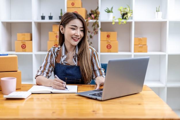 아름다운 아시아 사업가가 온라인 상점을 열고 노트북을 통해 고객의 주문을 확인하고 택배 회사를 통해 상품을 보내며 온라인 비즈니스를 여는 여성의 개념입니다.