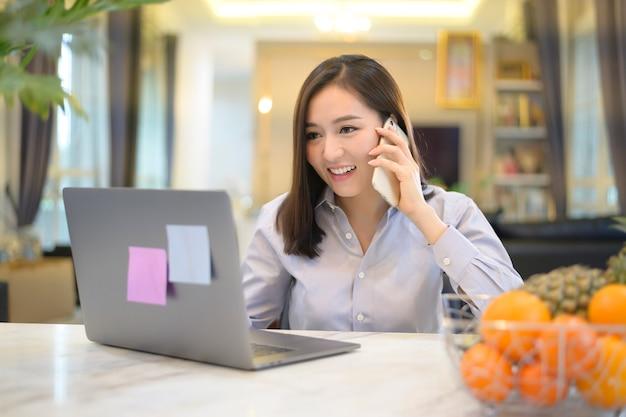 美しいアジアのビジネス女性が自宅でコンピューターを使用しています。