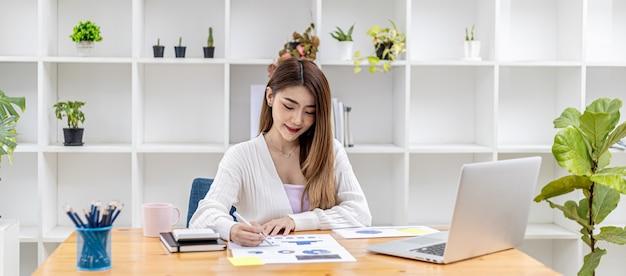 彼女はプライベートオフィスに座っている美しいアジアの実業家で、会社の財務書類をチェックしています。彼女はスタートアップ企業の女性幹部です。財務管理の概念。