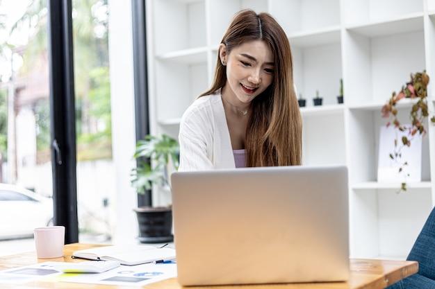 방에 서 있는 아름다운 아시아 여성 사업가는 노트북 메신저를 통해 파트너와 사업을 이야기하고 있으며 그녀는 신생 기업의 여성 임원입니다. 재무 관리의 개념