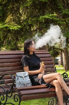 Красивая азиатская девушка курит вейп в общественном месте. вред курения