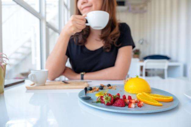 コーヒーを飲み、カフェでミックスフルーツとオレンジのケーキを食べる美しいアジアの女性