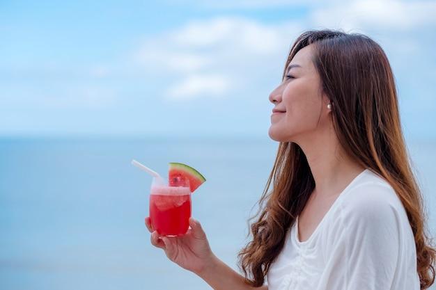 海のそばに座ってスイカジュースを飲む美しいアジアの女性