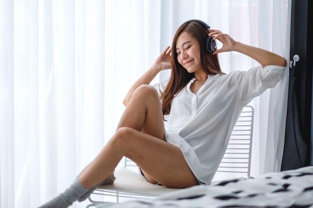 美しいアジアの女性は、寝室、幸福とリラクゼーションの概念でヘッドフォンで音楽を聴いて楽しむ