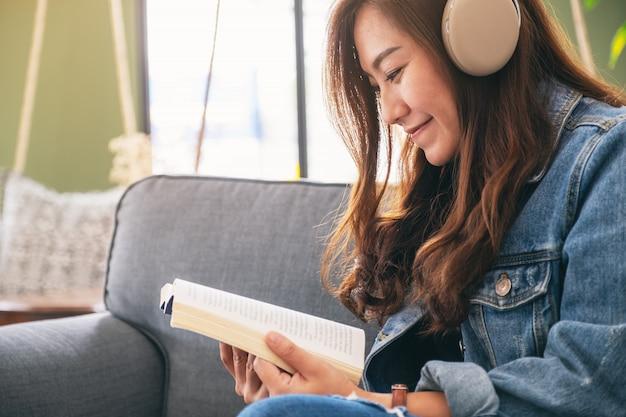 Красивая азиатская женщина наслаждается слушать музыку с наушниками во время чтения книги