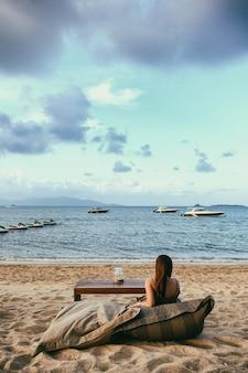 美しいアジアの女性は海岸沿いのビーチに座って楽しむ
