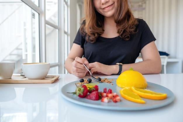 Красивой азиатской женщине понравилось есть апельсиновый торт с миксом фруктов ложкой в кафе