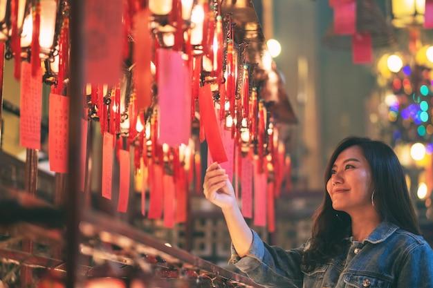 아름다운 아시아 여성은 중국 사원에서 빨간 램프와 소원을 바라보며 즐겼다