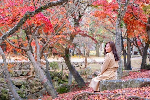 아름 다운 아시아 여자는 가을 배경에 붉은 색과 오렌지색 나무 잎 정원에 앉아 즐겼다