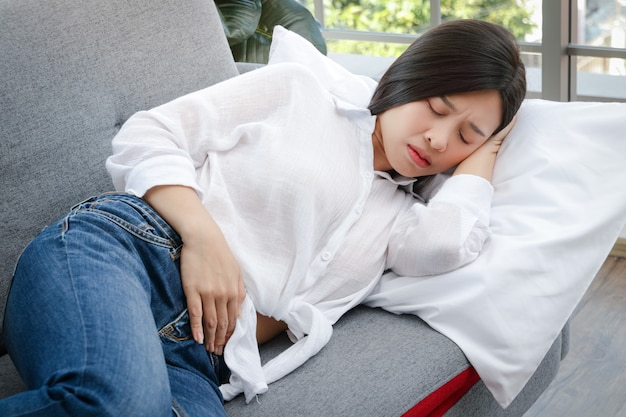 У красивой азиатской женщины болит живот, она лежит на диване в своей комнате дома. концепция больницы болезнь женщины. предупреждающие признаки болезней или боли в животе перед менструацией.