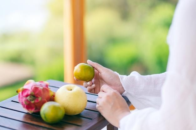 小さな木製のテーブルに梨とドラゴンフルーツとオレンジを保持している美しいアジアの女性