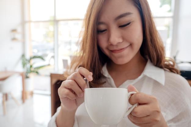 カフェで気持ちよくホットコーヒーを持って飲んでいる美しいアジアの女性