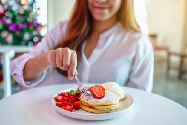 イチゴとフォークでホイップクリームとパンケーキを保持し、食べる美しいアジアの女性