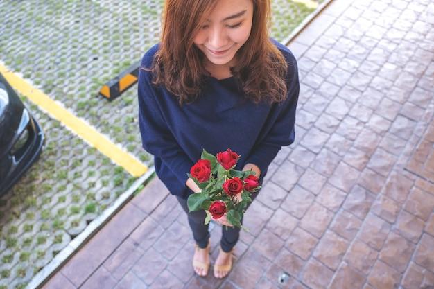 バレンタインデーに幸せな気持ちで緑豊かな庭園で赤いバラの花を保持している美しいアジアの女性