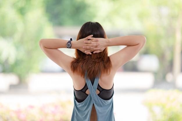 운동복을 입은 아름다운 아시아 여성이 집에서 운동하기 전에 스트레칭을 하고 있다