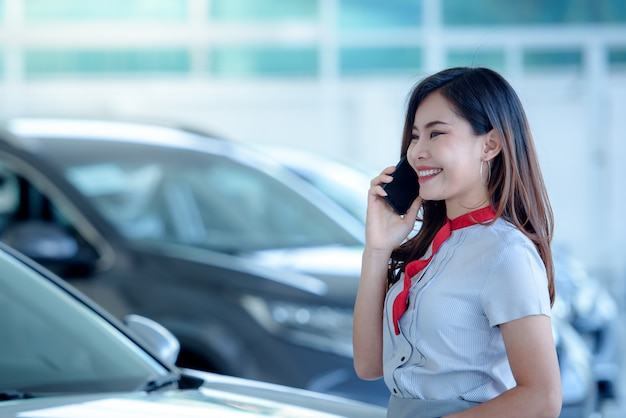 Красивая азиатская женщина с удовольствием продает новую машину в автосалоне и с удовольствием разговаривает по телефону. в восторге от хороших новостей онлайн в автосалоне.