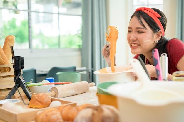 아름다운 아시아 여성이 집에서 빵집을 만들고, 라이브 스트리밍을 하거나 소셜 미디어에서 비디오를 녹화하고 있습니다.