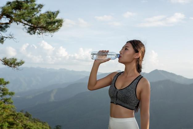 山の頂上で瞑想と運動をしている美しいアジアの女性。
