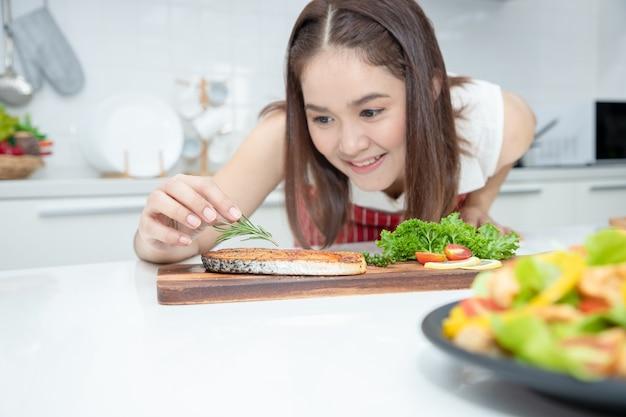 Красивая азиатка кладет розмарин на стейк из лосося, выложенный на тарелке с зелеными дубовыми овощами. идеи о здоровой кулинарии и похудании.