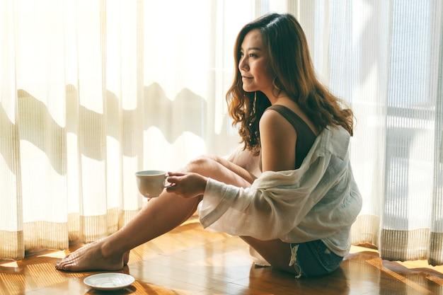 아침에 바닥에 앉아 뜨거운 커피 한 잔을 들고 있는 아름다운 아시아 여성