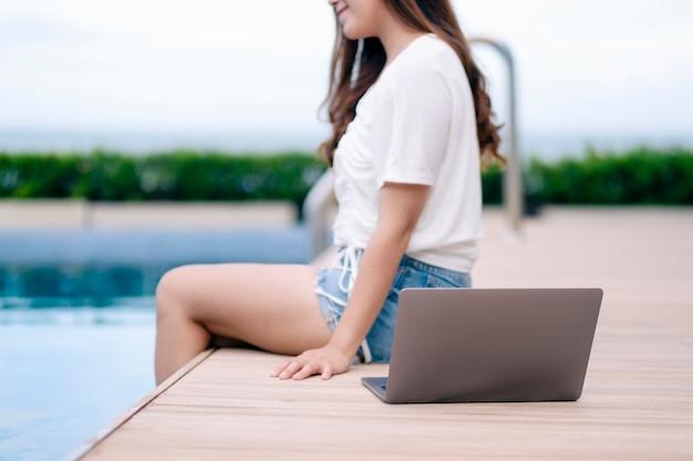 ラップトップコンピューターとプールのそばに座っている美しいアジアの女性