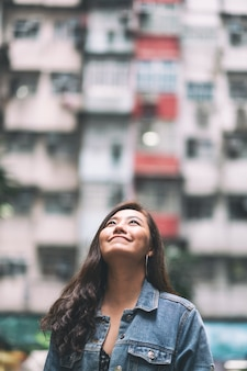 홍콩 쿼리 베이에 있는 커뮤니티의 붐비는 주거 건물 사이에 서 있는 아름다운 아시아 여성