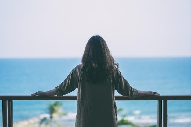 Красивая азиатская женщина стоит и любит смотреть на море на балконе