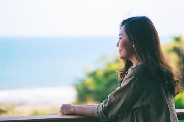 아름 다운 아시아 여자 서 발코니에서 바다 전망을 즐길 수