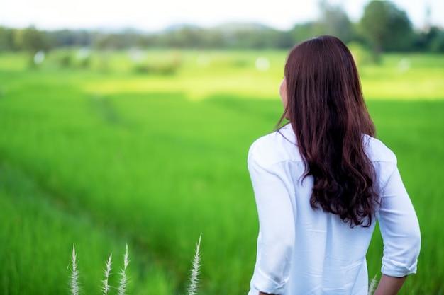 편안한 느낌으로 서서 푸른 논을 바라보는 아름다운 아시아 여성