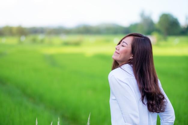 편안하고 행복한 느낌으로 푸른 논 앞에 서 있는 아름다운 아시아 여성