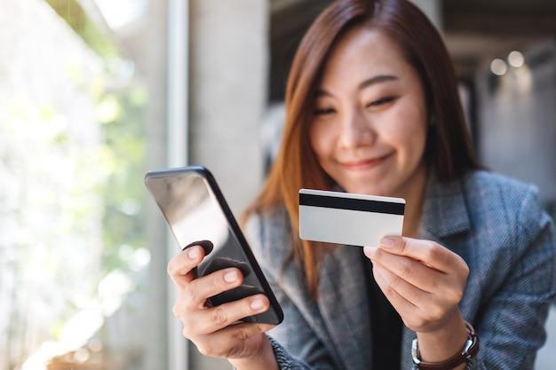 Красивая азиатская женщина с помощью кредитной карты для покупки и покупки онлайн на мобильном телефоне