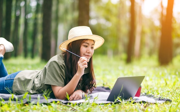 公園で横になっている間ラップトップコンピューターで作業し、入力する美しいアジアの女性