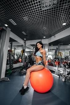 ジムでのフィットネスクラスの後、美しい運動セクシーな女の子がボールに座っています。フィットネス、ボディービル。