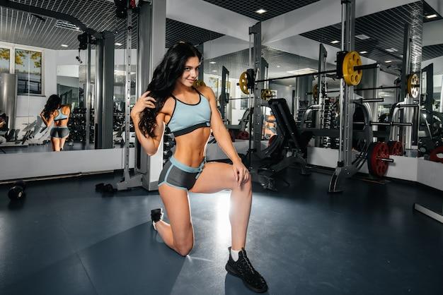 美しく、運動セクシーな女の子は、ジムでトレーニングし、フィットネスを行います。フィットネス、ボディービル