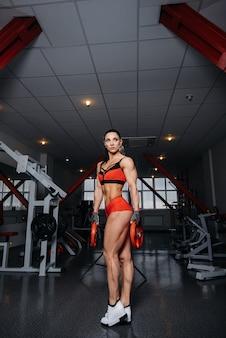 美しく、運動セクシーな女の子は、ジムでトレーニングし、フィットネスを行います。フィットネス、ボディービル。