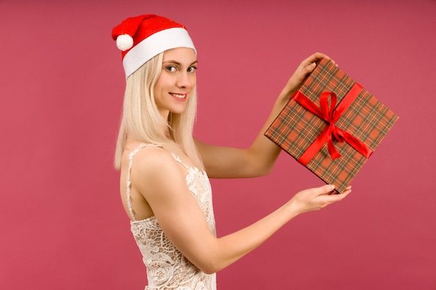 새해 모자와 흰색 드레스를 입은 아름다운 운동 트랜스젠더 남자가 선물을 손에 쥐고 있습니다. 루비 배경에 크리스마스 또는 새해 축하