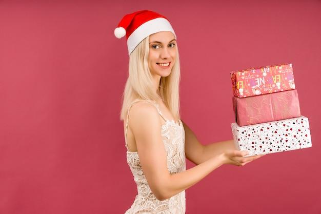 Красивая спортивная женщина в новогодней шапке и белом платье, держит в руках подарки