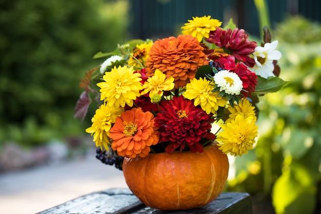 Красивый осенний букет в тыкве на деревянной скамейке в саду сад цветы день благодарения