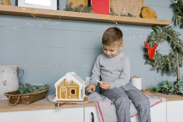Красивый мальчик сидит на кухонном столе и украшает пряничный домик