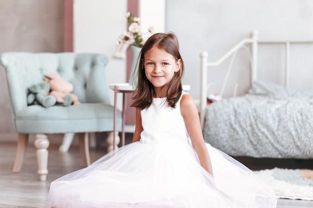 美しい女の赤ちゃんは、白いドレスを着た明るい寝室の床に座っています。カメラを見てください