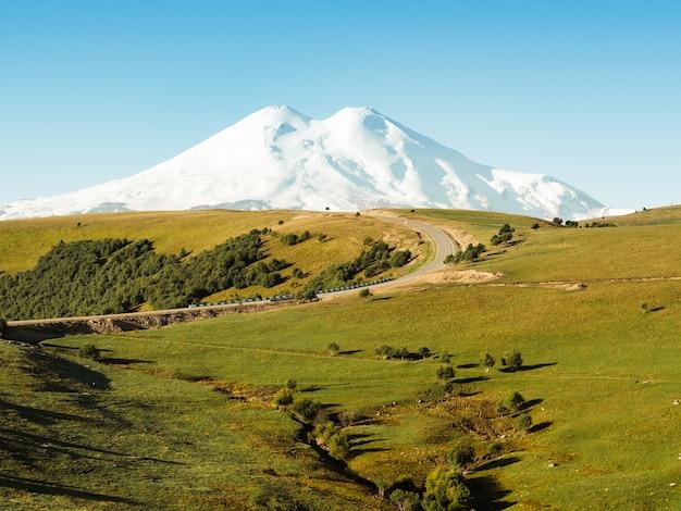 Красивый поворот дороги через зеленые холмы кавказа на эльбрус.
