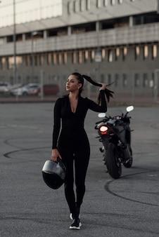 建物の外の次のスーパーバイクのヘルメットを保持している美しいバイカーの女性。