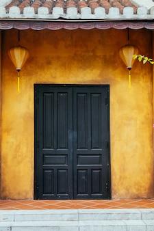 Красивая черная деревянная дверь на желтой стене с китайскими фонариками. древний город хойан. вьетнам.