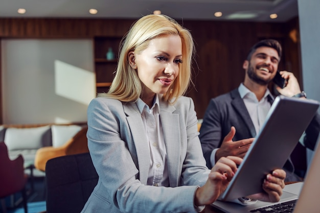 비즈니스에서 아름다운 금발 아가씨는 태블릿을 사용하여 비즈니스 소셜 미디어를 확인합니다.