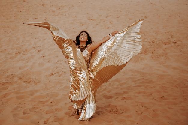 Красивая белокурая женщина в блестящем платье с крыльями в костюме танцует восточный танец в пустыне на песке. красивая экзотическая танцовщица в костюме для танца живота.