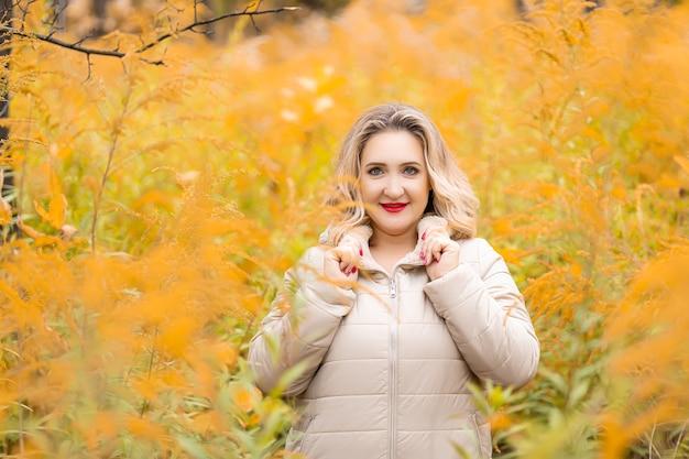 Красивая блондинка девушка стоит возле желтого куста в пуховике