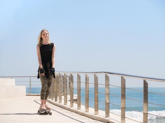 海辺の夏の暑い日にスケートボードにバックパックを持った美しいブロンドの女の子。