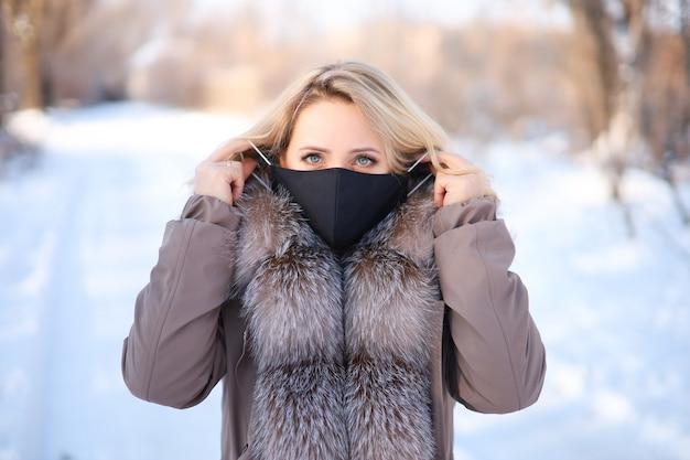모피 칼라가있는 모피 코트의 아름다운 금발이 검은 색 보호 마스크를 착용합니다.